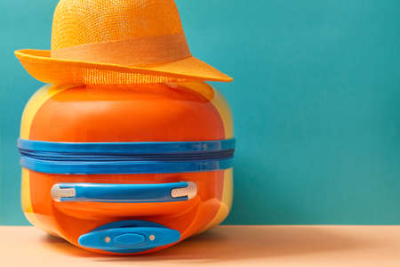 Travelling background. Summer holidays. Travelling abroad. Bright suitcase and sun hat, copy space. Vacation concept