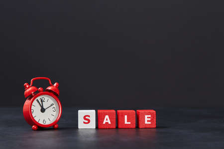 Time to sale. Black friday. Sell-out. Total sale. Red cubes with one white, alarm clock on dark background, copy space