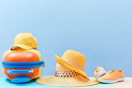 Travelling background. Family trip. Family holiday. Summer time. Suitcase, sun hats and sneakers on blue, copy space.