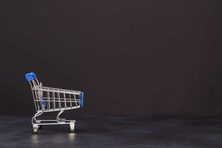 Big sale. Black friday shopping. Best offer. Sell-out and discount concept. Trolley on dark background, place for text.