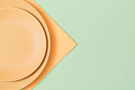 Festive dinner. Festive table setting. Holiday celebration. Empty beige plate and napkin, isolated on green. Copy space