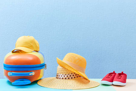 Family trip. Travelling background. Family holiday. Summer time. Suitcase, sun hats and sneakers on blue, copy space