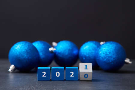 Happy new year. Holiday decoration. Festive christmas decor. Wooden cubes in line with numbers, blue balls with glitter