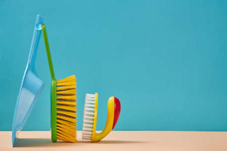 Cleanup. Sweeping. Cleaning supplies. Brush with handle and trowel isolated on blue background. Copy space for text