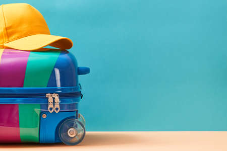 Time to travel. Summer vacation. Travelling abroad. Summer holidays. Colourful suitcase and cap on top, place for text