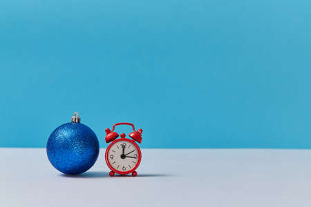 Bright shiny ball for decor. Red clock showing twelve oclock. Happy new year. Xmas concept. Copy space. Blue backdrop
