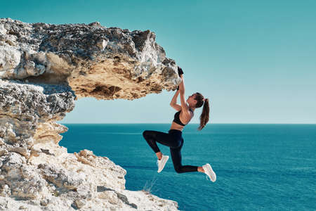 Rock climbing. Sport. Active lifestyle. Athlete woman hangs on sharp cliff. Seascape. Outdoors workout. High resilience Stockfoto