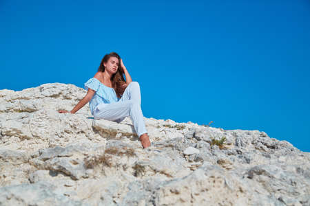 Woman sitting on rock and looking away. Relaxing moment and dreaming. Feeling of calm. Contemplation and comprehension.