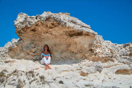 Dreamy woman sitting in shade under rock. Contemplation or Peace of mind idea. Feeling of calm orTime to rest idea.