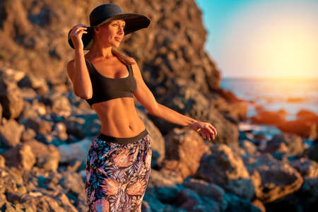 Sweet lady with pensive look. Mountains on background. Sunset and nature view. Relaxation and beach concept, copy space