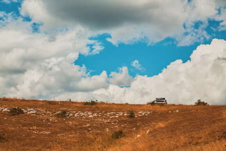 Luxury car riding on path. Mountain terrain, cloudy sky. Travel and adventure. Future and new way concept, copy space Фото со стока