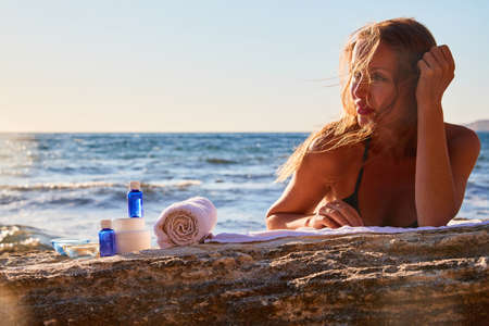 Spa treatment and total relaxation concept. Woman sunbathing on cloth. Beauty products on rock. Seascape and nature.