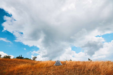 Virgin nature and camping concept. Grey tent and chair on dry grass. Empty meadow for rest. Fresh air and new adventure.