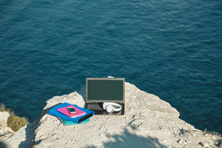 Laptop, headphones and folders with documents on sea rock. Seascape on background. Freelancing and remote work idea 写真素材
