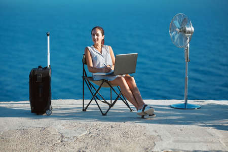 Business travelling and remote work concept. Life work balance, freelance idea. Woman working with laptop on beach.