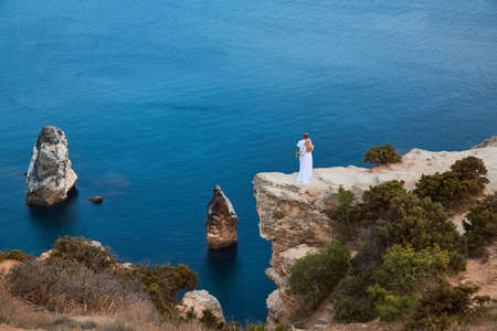 Newly-weds enjoy beautiful ocean view on cliff. Calm sea and water texture. Nature and festive event idea, copy space 写真素材
