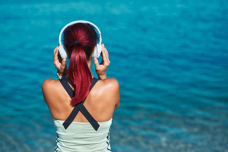 Woman posing with back wearing white headset. Female enjoying ocean view. Contemplation and meditation time concept