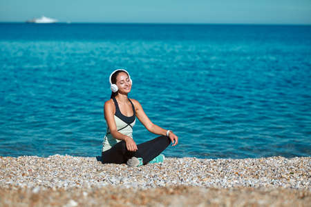 Cute lady enjoying sun sitting on beach. Girl listen to music in headset. Contemplation and meditation time concept 写真素材