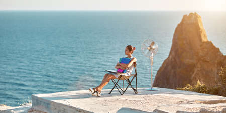 Life and work balance, freelance concept. Lifestyle change idea. Pensive woman holding documents, sitting on seashore.
