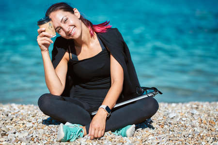Smiling woman with cup of coffee and laptop sitting on beach. Enjoy summer trip to sea. Remote office, travel time idea