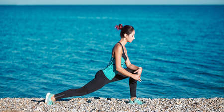 Woman in sportswear trying to sit on split. Lovely ocean view and rocky coastline. Yoga and healthy lifestyle concept