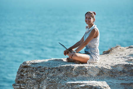 Cheerful woman sitting on rock with laptop. Work from any country. Freelance job travelling and remote office concept