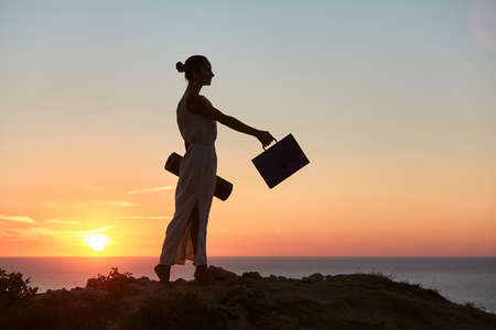 Businesswoman posing on sea sunset landscape. Remote work and business travelling idea. Life and work balance idea