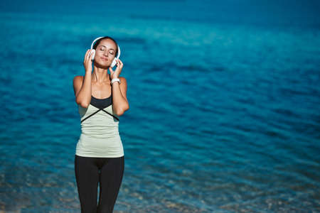Woman enjoying music in headset. Calm sea and fresh air. Meditation time and contemplation nature concept, copy space 写真素材