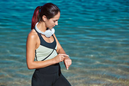 Female sets timer for workout. Lady in sportswear and headset. Training out on fresh air. Sport time and fitness idea