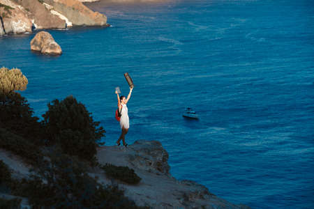 Happy woman with hands up posing on edge of cliff. Lifestyle change or goal achievement concept. Thirst for travel idea