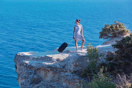 Thirst for travel and lifestyle change concept. Smiling woman with suitcase posing on sea rock. Seascape on background.