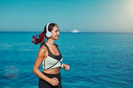Woman running along ocean. Fresh air and virgin nature view. Active sport time fitness and healthy lifestyle concept 写真素材