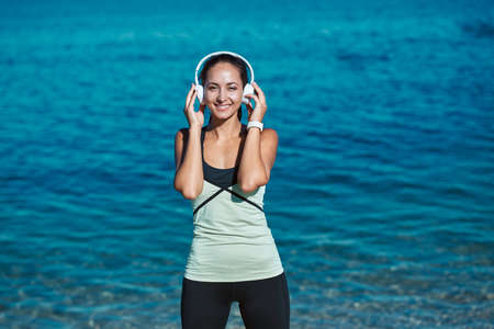 Pretty lady listen music wearing headset. Stylish sportswear for workout. Fresh air and nature. Sport and fitness idea