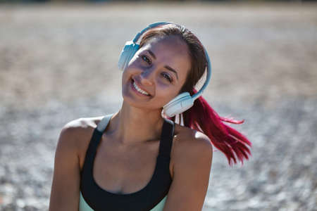 Smiling woman posing wearing white headset. Lady enjoying music on beach. Contemplation and healthy lifestyle concept