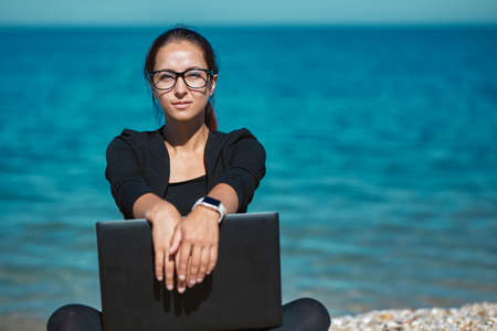 Clever woman sitting on beach with laptop. Cute seascape on backdrop. Travel time and freelance job idea, copy space