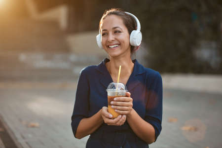 Cheerful laughing female holding cup of drink. Woman wearing white headset outdoors. Take break and coffee time concept