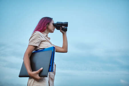 Woman looking forward in binoculars. Lady holding laptop and folder. Goal setting and new horizons concept, copy space