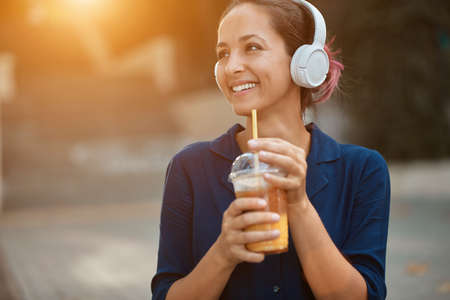 Smiling cheerful woman enjoy beverage. Lady listen music in headset. New emotions, street style and city walk concept