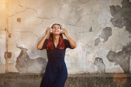 Woman in dress with white headset. Lady posing on old wall backdrop. Listen music and street style concept, copy space