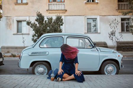 Woman with pink hairstyle sitting on car background. Old vintage automobile on street. New place and new emotion idea 写真素材
