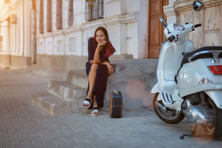 Lady sit on step with suitcase. White motorbike on right side and building on backdrop. Travel time and new place idea