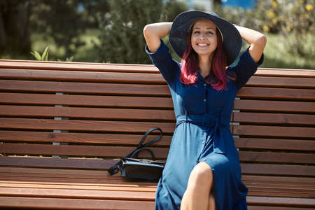 Smiling woman sitting on bench in park. Cute lady in hat and blue dress. Leisure time, take break and new emotion idea