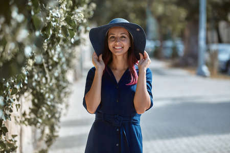 Beautiful woman in stylish hat posing near greenery. Sunny weather on nature. Leisure time and new adventure concept