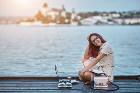 Woman in glasses sit near water. Freelance job and travel concept. Distance learning and new ground idea, copy space 写真素材