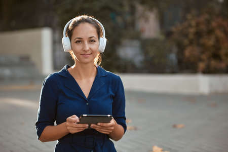 Cute woman holding tablet and wearing headset. Lady enjoying spare time. New emotions and street style idea, copy space