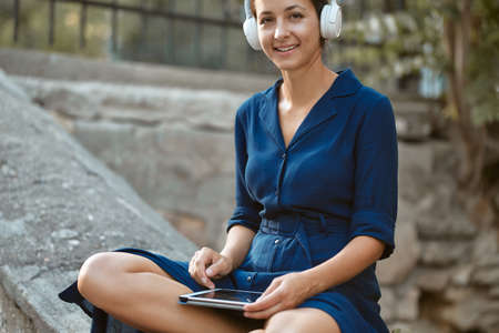 Smiling woman listen music in headset with modern tablet. Relax and joy in park. Leisure time and take break concept