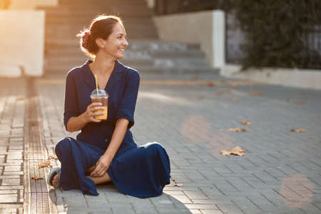 Take break and coffee time concept, copy space. Attractive woman in blue dress sitting on ground. Spare time on nature.