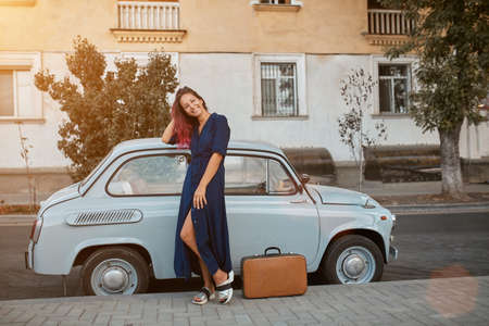 Travel time and new places idea, copy space. Woman in blue dress and suitcase on ground. Old vintage car on background 写真素材