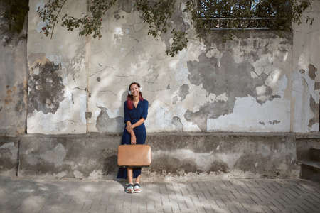 Happy lady posing on street on old wall background. Woman in headset holding suitcase. Travel time and new place idea