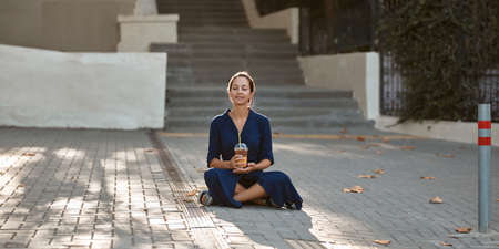 New place, street style and new emotion concept, copy space. Cute laughing woman drinking beverage sitting on ground